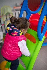 Little girl have fun and climbs a slide.