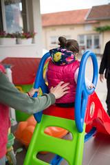 Mom holding her daughter on slide. Back view