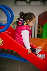 Little girl have fun on colorful slide.