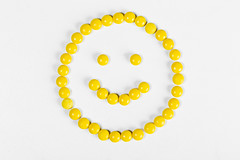 Smiley face from yellow pills on white background, top view
