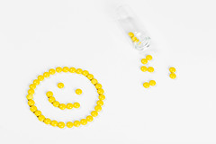 A smile made of yellow pills on a white background