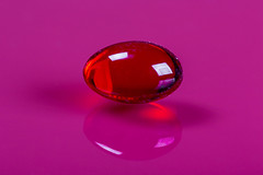 Red capsule on pink background. Medical healp concept