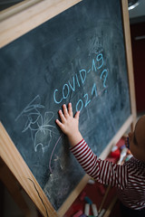 Education about Covid-19. Baby`s hand on small chalkboard.