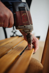 Man building wooden furniture. Hand and electric drill closeup.