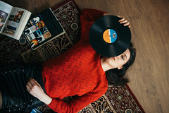 Young woman enjoying at  home listening to vinyl records from above.