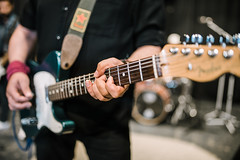 Guitarist performing live. Closeup of fingers on electric guitar neck.