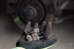 Mechanic holding lug nuts in his hand and a brake disc in the blurry background