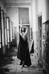 Bw photo of lonely girl dancing in abandoned house. Back view.