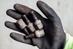 Mechanic holding lug nuts in his hand