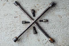 4-way wrench and lug nuts on the ground