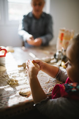 Little girl have fun with dough in the kitchen.