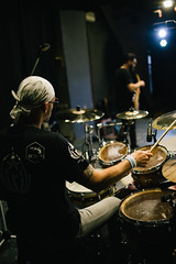 Back view of attractive tattoed musician playing drums on stage live.