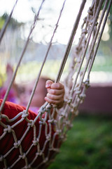 little hand holding a rope of a swing outdoors.