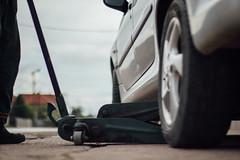 Reifentechniker hebt ein Auto mit einem Wagenheber an