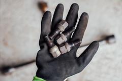 Mechaniker hält Radmuttern in seiner Hand, Kreuzschlüssel auf dem boden im unscharfen Hintergrund