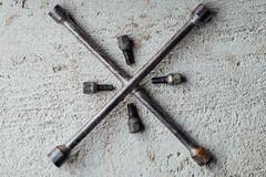 Kreuzschlüssel und Radmuttern auf dem Boden