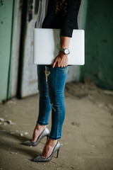 Business woman standing and holding Macbook.