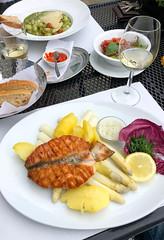 Teller mit gegrilltem Lachs, Kartoffeln, weißen Spargeln, Zitrone, Kräutern, Radicchio und Dip