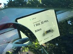 Display von Elektroauto zeigt verbleibende Zeit und Kilometer, bevor das Auto aufgeladen werden muss