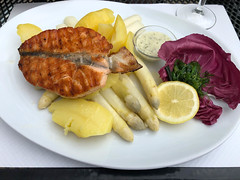 Grilled salmon fillet with boiled potatoes, white asparagus, lemon, dip and radicchio on a plate