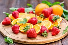 Fresh ripe sliced oranges and strawberries