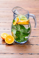 Jug with orange and mint lemonade on a wooden background