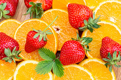 Fruit background with fresh orange slices and strawberries