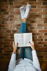 Woman reading a book. Legs up the wall pose.