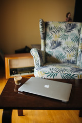 Coffee and Macbook in the living room with vintage armchair in the background.