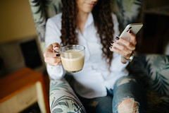 Business woman using smartphone and enjoying of cappuccino.
