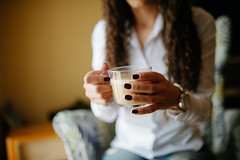 Businesswoman holding a glass of hot coffee closeup.