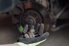 Mechaniker hält Radmuttern in seiner Hand und Bremsscheibe im verschwommenen Hintergrund