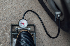 Reifendruck wird mit einer Fußluftpumpe überprüft