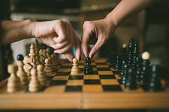 Hands playing chess on a wooden board at home