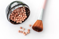 Scattered blush balls on a white background with a brush