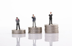 Miniature model of businessman standing on coin stacks
