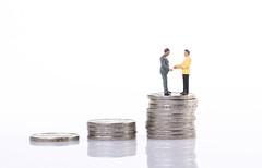 Businessman handshake on top of coin stacks