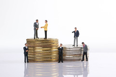 A group of miniature businessman on stack of coins closeup
