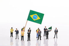 Miniature people with flag of Brasil