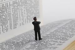 Miniature businessman figure standing on book