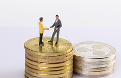 Two miniature people standing on coins