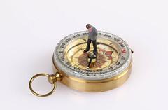 Businessman figure standing on compass