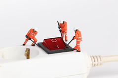 Workers on white electric splitter with red switch