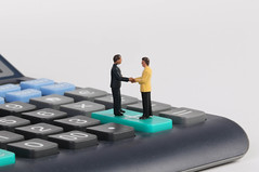 Two businessman shaking hands while standing on calculator