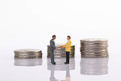 Businessman handshake in front of coin stacks