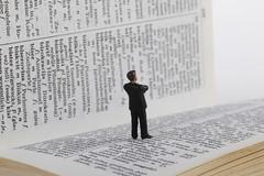 Businessman figure standing on book