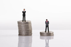 Close up of businessman miniature people figures standing with stack of coins