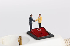 Businessman shaking hands on white electric splitter with red switch