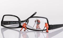 Miniature technician repairing reading glasses. Business concept