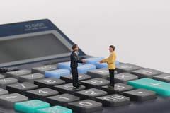 Two businessman standing on calculator